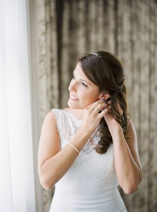 bride-in-bridal-suite-hair-pulled-back-soft-curls-the-white-dress-bridal-gown-ring-bracelet-headband