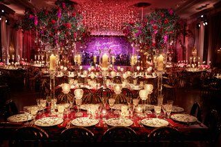 opulent-luxury-wedding-reception-trees-purple-neon-sign-red-candlelight-flowers-greenery