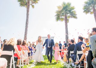 bride-and-groom-walking-up-aisle-with-flower-girl-and-groom-daughter-step-daughter-flower-petal-toss