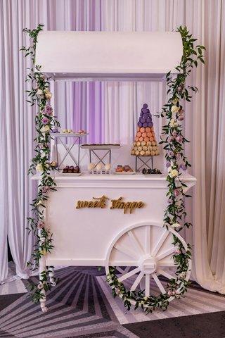 wedding-reception-dessert-cart-idea-macaron-tower-desserts-on-trays-garland-flowers