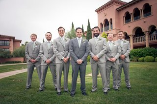 groomsmen-in-grey-suits-with-light-green-ties-and-natural-boutonnieres-groom-in-darker-grey-suit