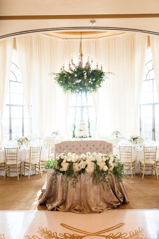 tufted-love-seat-for-sweetheart-table-with-metallic-linens-and-arrangement-of-white-flowers-foliage