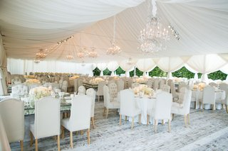 tent-wedding-reception-chandeliers-whitewash-wood-flooring-beige-dining-chairs-glass-crystal-tables