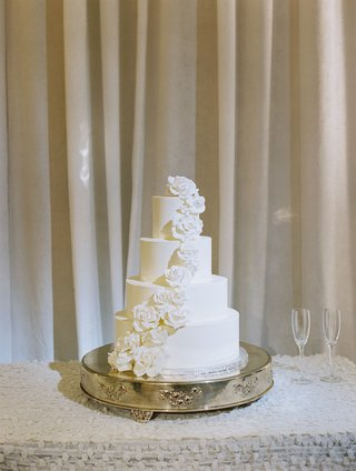 four-layer-white-fondant-wedding-cake-on-stand-with-sugar-flower-roses-going-down-side
