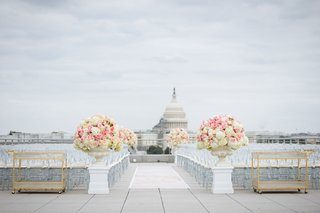 rooftop-wedding-ceremony-clear-guest-chairs-gold-bar-carts-white-pink-flowers-view-of-capitol