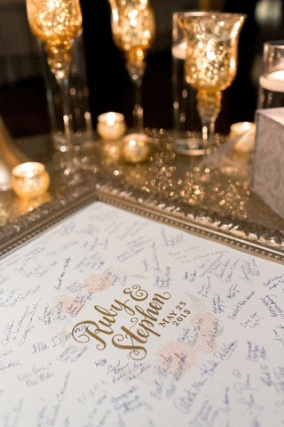 wedding-reception-with-a-gold-frame-bride-and-grooms-name-surrounded-by-flowers-guest-signatures