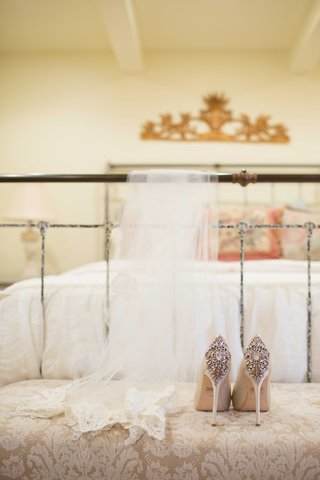 white-bridal-veil-and-white-tan-champagne-high-heel-shoes-on-cushion-near-white-bed