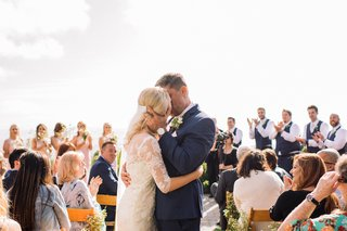 groom-in-navy-blue-suit-kisses-bride-in-middle-of-aisle