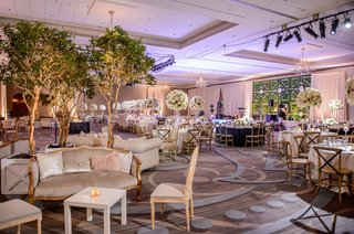 wedding-reception-ballroom-lounge-area-settee-armchair-live-trees-inside-ballroom-purple-lighting