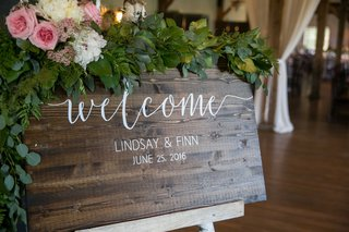 welcome-sign-on-wood-plaque-greenery-pink-white-flower-white-writing