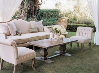 plush-sofa-chair-and-wood-coffee-table-on-grass-at-wedding-reception
