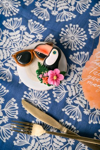wedding-reception-styled-shoot-tropical-theme-blue-linen-gold-flatware-orange-sunglass-and-toucan