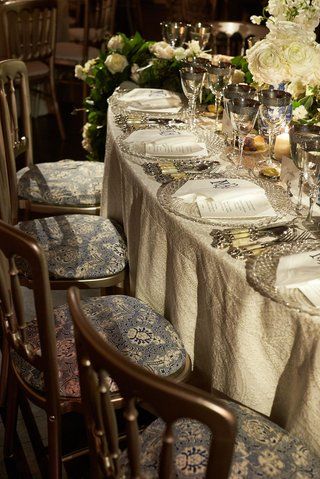 wedding-reception-luxe-linens-blue-and-white-pattern-chair-cushions-silver-backs-bone-china-silver