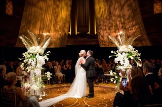bride-and-groom-between-calla-lily-orchid-hydrangea-rose-gold-palm-flower-arrangement-in-the-round