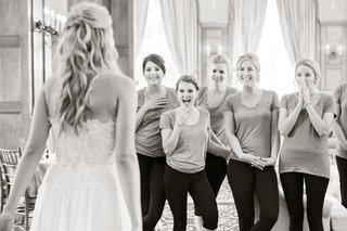 black-and-white-photo-of-bridesmaids-reacting-to-the-brides-complete-look