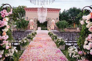flower-petal-aisle-pink-orange-rose-bush-decorations-flowers-on-wrought-iron-gate-chandelier