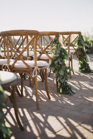 arrangement-of-eucalyptus-leaves-on-wooden-wedding-ceremony-chairs