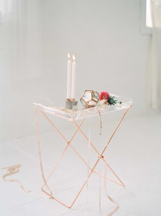 a-contemporary-style-copper-and-glass-table-with-candles-a-geometric-shape-and-a-flower-bar-cart