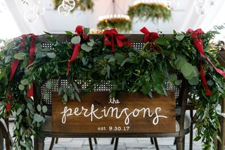 wedding-reception-seating-cane-back-chair-wood-sign-calligraphy-garland-red-ribbon-wedding-ideas
