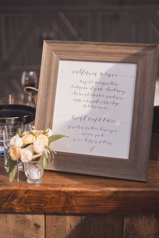 calligraphy-sign-by-laura-hooper-in-rustic-wood-frame-on-wood-bar-at-outdoor-winery-wedding