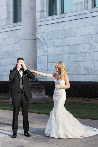 groom-in-tuxedo-and-bow-tie-covers-eyes-as-bride-taps-on-his-shoulder-during-first-look
