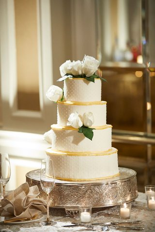 four-layer-wedding-cake-on-silver-cake-stand-white-rose-green-leaves-swiss-dot-gold-border-tiers