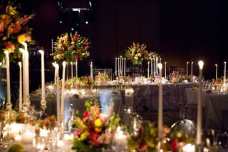 dark-wedding-reception-space-tall-candles-flowers-in-clear-boxes-translucent-ghost-chairs