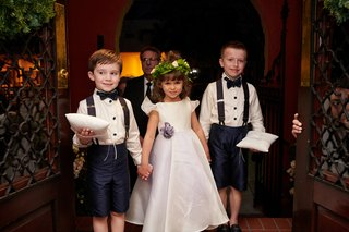 two-ring-bearers-in-shorts-and-suspenders-hold-hands-with-flower-girl-in-floral-crown