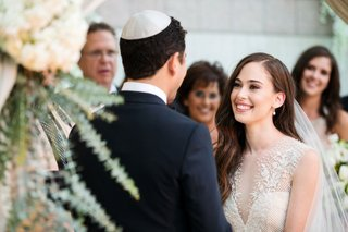 bride-smiles-at-groom-in-yarmulke-at-jewish-wedding-ceremony-chuppah-sabrina-dahan-dress