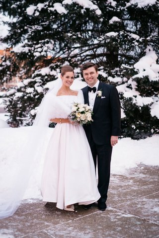 bride-and-groom-portrait-bride-in-white-fur-wrap-snow-on-trees-mothers-wedding-dress-groom-bow-tie