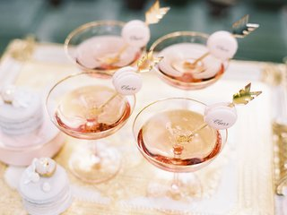 wedding-cocktail-hour-gold-bar-cart-coupe-glass-with-rose-champagne-and-cheers-macaron-on-arrow