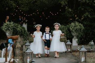 two-cute-flower-girls-white-dresses-moss-baskets-ring-bearer-in-suspenders-high-socks-bow-tie