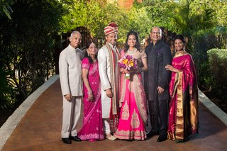 indian-bride-in-hot-pink-and-gold-sari-with-groom-and-parents-mothers-in-fuchsia-saris