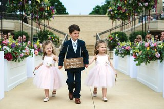 ring-bearer-with-wooden-sign-around-neck-holds-hands-with-two-flower-girls-in-blush-dresses