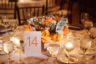 table-14-in-orange-on-round-reception-table-with-orange-rose-and-dusty-miller-curly-willow-branch