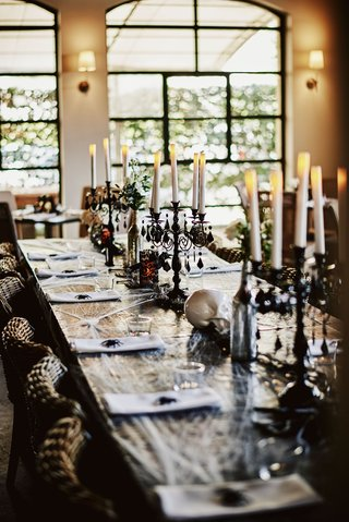 wedding-reception-table-long-with-cobwebs-spider-black-candelabra-skulls-wicker-chairs