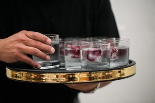 gold-border-serving-platter-with-water-glasses-with-flower-petals-in-ice-cubs