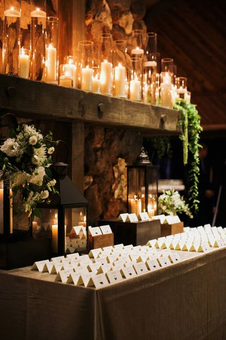 escort-cards-on-table-in-front-of-lanterns-and-lots-of-candles-in-tall-hurricanes