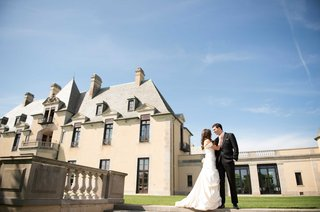 bride-in-pnina-tornai-wedding-dress-and-groom-in-tuxedo-in-front-of-oheka-castle