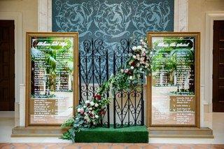 wedding-reception-seating-chart-mirror-gold-frames-iron-gates-garland-greenery-burgundy-pink-white