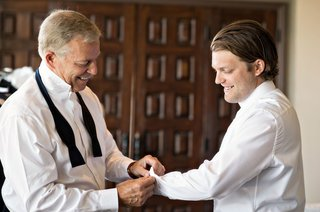 groom-in-white-button-down-shirt-with-father-of-groom-in-undone-bow-tie-helping-son-with-cufflinks