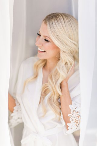 wedding-day-getting-ready-long-blonde-curled-hair-white-robe-graphic-lace-trim-curtains