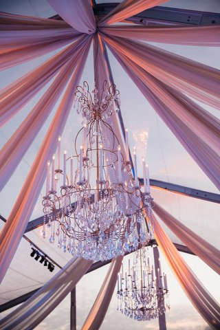 golden-chandeliers-with-faux-taper-candles-and-crystals-suspended-from-clear-tent-with-draping