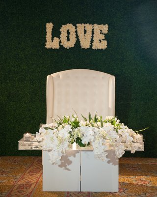wedding-sweetheart-table-nfl-player-levine-toilolo-wedding-love-sign-in-flowers-on-hedge-wall