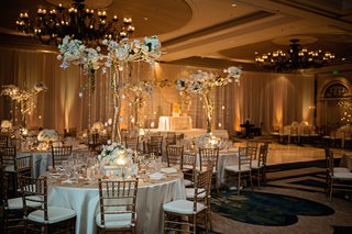 candlelit-reception-hall-with-gilt-chairs-and-ivory-linens