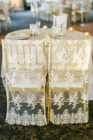 wedding-reception-sweetheart-table-gold-chairs-with-lace-sheer-covers-round-table-champagne-in-ice