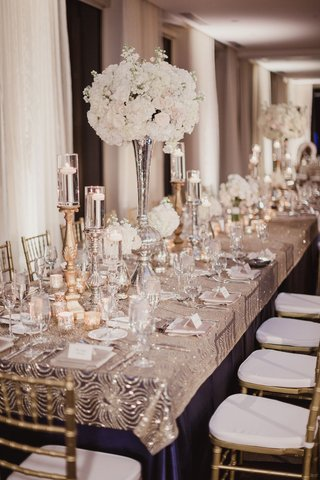 wedding-reception-sparkle-decor-navy-linen-metallic-overlay-gold-candlestick-white-flowers