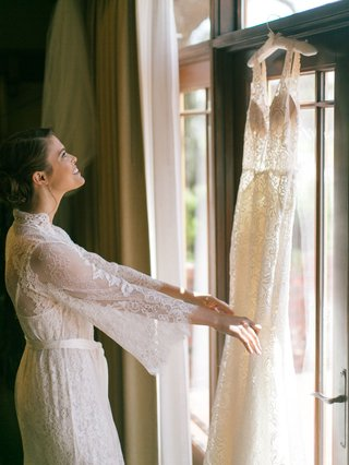 bride-in-lace-robe-looking-at-wedding-dress-hanging-in-window