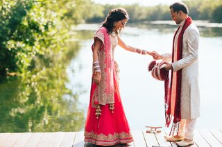 indian-bride-in-gold-and-magenta-sari-with-groom-in-traditional-white-and-red-outfit