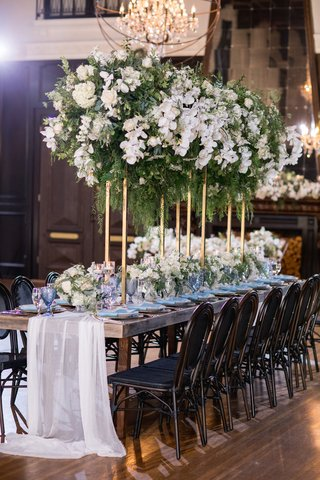 long-wooden-table-with-sheer-white-fabric-runner-and-white-and-green-centerpiece-on-gold-stand